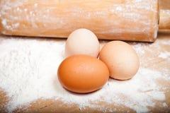 Ägg på mjöl med träkavlen Arkivbild