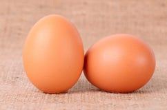Ägg på säckvävbakgrund Arkivfoto