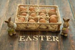 Ägg på sugrör som förläggas med rolig kanin två till easter garnering Royaltyfria Foton
