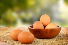 Ägg på trätabell- och suddighetsnaturbakgrund Royaltyfri Bild
