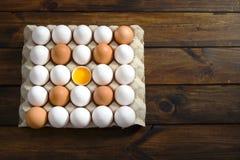 Ägg paketerar med det vita och bruna ägget och öppnar ägget i mitt, Arkivfoton