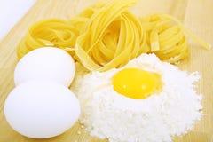 Ägg, pasta och mjöl på träskrivbordet Royaltyfri Foto