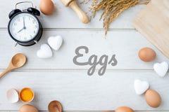 Ägg smsar bokstaven på det vita köksbordet med nya rå ägg, ägg för gul äggula, det vita hjärtaformtecknet och den klassiska tappn arkivfoton