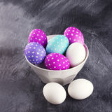 Ägg som dekoreras för påsk i en vit bunke mot en mörk backgro Arkivbild