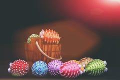 Ägg som dekoreras med ljus färg, dragar och pryder med pärlor på svart Royaltyfri Fotografi