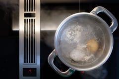 Ägg som lagar mat i vatten i en kruka på en ugn Royaltyfria Bilder