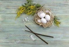 Ägg, stearinljus, rökelse och filialer av en mimosa Arkivfoton