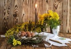 Ägg, stearinljus, rökelse och filialer av en mimosa Royaltyfria Bilder