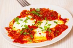 Ägg tjuvjagade i en sås av tomater, chilipeppar och lökar Arkivfoton