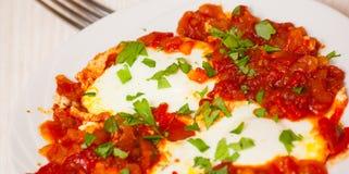 Ägg tjuvjagade i en sås av tomater, chilipeppar och lökar Fotografering för Bildbyråer