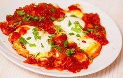 Ägg tjuvjagade i en sås av tomater, chilipeppar och lökar Arkivfoto
