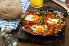 Ägg tjuvjagade i tomatsås, och andra grönsaker tjänade som med bröd Arkivfoto