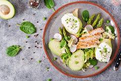 Ägg tjuvjagade på rostat bröd med den avokado-, sparris- och hönafilén på galler Fotografering för Bildbyråer