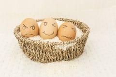 Ägg tre i en brun korg på ris Arkivfoton