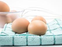 Ägg tre på tyg och ägg i klar kopp Arkivbild