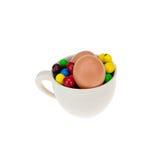 Äggen och godisen är i en kopp kaffe som avskiljs av en vit Royaltyfria Foton