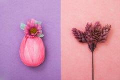 Ägget slås in i gåvarosa färgpapper med den mintkaramellgräsplanbandet och blomman Kvist av en växt med kottar som i flygturer på Royaltyfria Foton