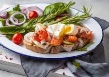 Ägget tjuvjagade och laxen på rostat bröd med grönsaker Royaltyfria Bilder
