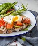 Ägget tjuvjagade och laxen på rostat bröd med grönsaker Arkivfoto