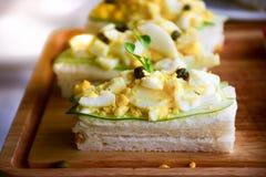 Äggsalladsmörgåsar med gurkaskivor arkivbild