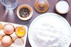 Äggskal, äggula och mjölet på en platta, ett exponeringsglas av vatten Royaltyfri Bild