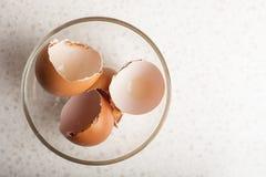 Äggskal i en glass bunke på en vit tabell Arkivbild