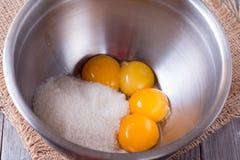 Äggulor och socker i metallbunke Royaltyfri Bild