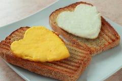Äggviteämne- och äggyolk på en rostat bröd Arkivbilder