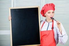 Ägnat till matlagning- och matförberedelsen Gullig flicka som slickar skeden på svart tavla Ledar- kock som ger matlagninggrupp fotografering för bildbyråer