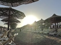 Ägypten: Einsamer Strand ausgerüstet mit Sonnenbetten und -regenschirmen - am Abend, bei Sonnenuntergang stockfotos