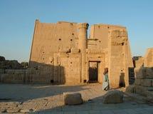 ÄGYPTEN, am 15. Januar 2005: Riesiger Mast am Eingang zu Horus-Tempel von Edfu und von altem Beduinen Lizenzfreie Stockfotografie