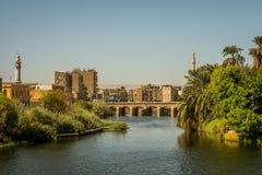Ägyptische Stadt im Sonnenuntergang mit zwei minaretes und einer Brücke Eine Ansicht von einer Kreuzfahrt auf dem Fluss Nil, Ägyp lizenzfreie stockfotografie