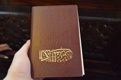 Ägyptisches orthodoxes Christian Bible Buch Browns mit Goldarabischen Buchstaben von einem Mann in einer Hand in einer Kirche stockfotos