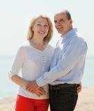 Äldre älska par som omfamnar mot havet Royaltyfria Bilder