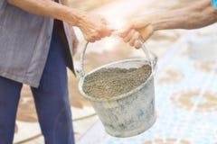Äldre arbete eller arbetare som bär konstruktionssand för blandning med cement och bygger hus Arkivbild