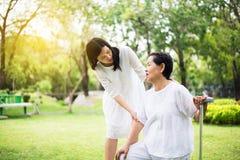 Äldre asiatiska kvinnor som faller, medan gå för att göra fysiskt med den utomhus- pinnen, vaktmästare, tar omsorg och service, s royaltyfri fotografi