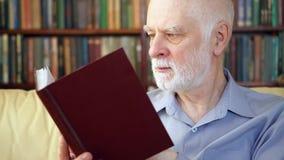 Äldre avslappnande hemmastadd läsebok för hög man som tycker om avgång Bokhyllor i bakgrunden stock video