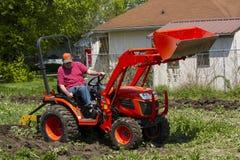Äldre bonde Plowing His Garden med en kompakt traktor Arkivfoto