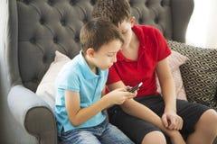Äldre broder på soffan och yngre bror som spelar mobil pho Royaltyfria Bilder
