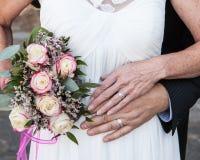 Äldre brud och brudgumhänder och cirklar med blommor Arkivfoton