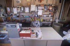 Äldre butiksinnehavare bak kassaapparaten, Yountville, NM royaltyfria foton