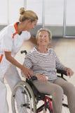 Äldre dam på rullstolen och hennes omsorgdonator arkivbilder