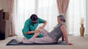 Äldre dam som hemma rehabiliteras av en fysioterapeut lager videofilmer