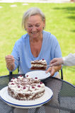 Äldre dam som tycker om en skiva av kakan Royaltyfria Foton