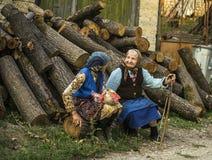Äldre damer, farmödrar i byn med Wood bakgrund Arkivbild