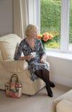 Äldre damsammanträde i en stol som dricker te Arkivfoton