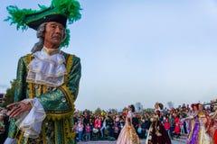 Äldre dansare i ljusa historiska medeltida dräkter som dansar i fyrkanten i sommar fotografering för bildbyråer