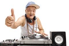 Äldre discjockey som spelar musik och gör tummen upp tecken Arkivfoton