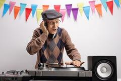 Äldre discjockey som spelar musik på en skivtallrik arkivbilder