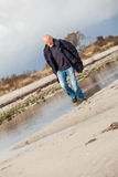 Äldre driftig manspring längs en strand Royaltyfri Fotografi